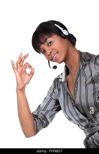 A businesswoman with a headset on making an ok sign. - Stock Image