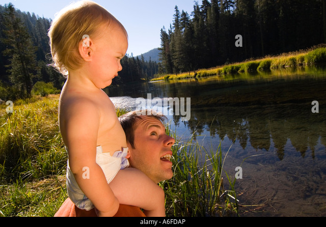 A baby sitting on her fathers shoulders by the Truckee River near Tahoe City California - Stock-Bilder