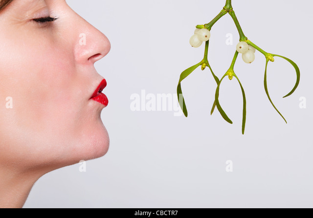 Photo of a woman with her eyes closed and red lipstick on waiting to be kissed under the mistletoe. - Stock-Bilder