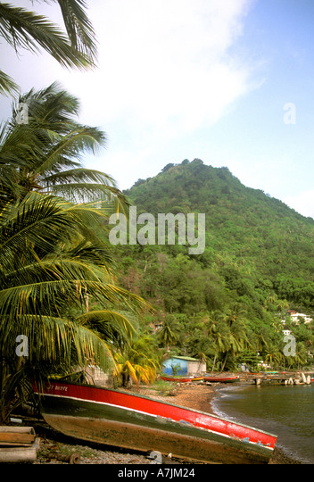 Dominica West Indies Caribbean Fishing Boat on Beach Mountain Background - Stock Image