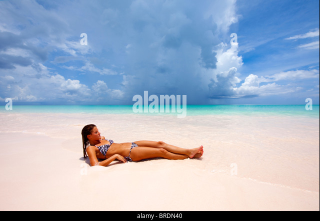 young bikini clad woman sunning on deserted beach - Stock Image
