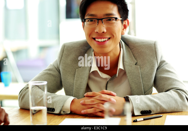 Happy asian man sitting at the table in office - Stock Image