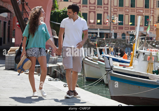 Couple walking by urban pier - Stock Image