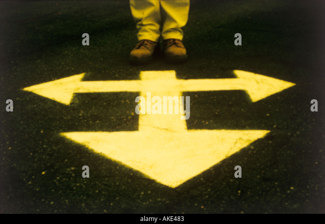 one persons feet standing by direction arrows - Stock Image