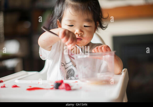 One year old baby girl eating fruit in highchair - Stock Image