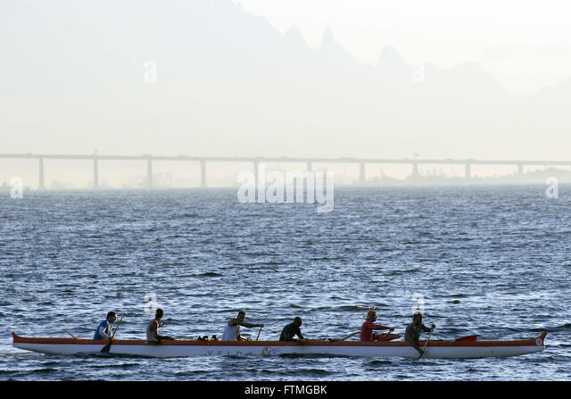 Practice canoeing in Guanabara Bay to Niteroi-Rio Bridge in the background - Stock Image