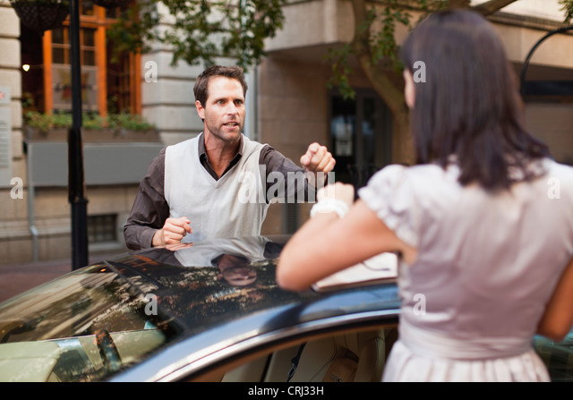Couple arguing over sports car - Stock Image