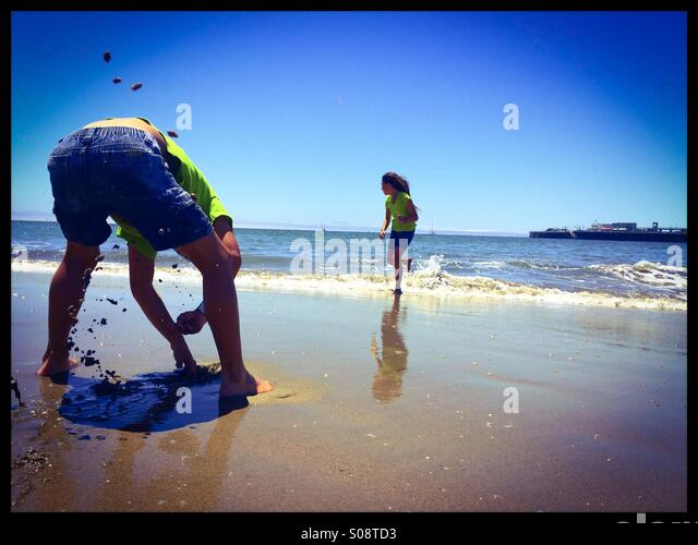 A ten year old and six year old brother and sister play at Seabright State Beach. Santa Cruz, California, USA - Stock-Bilder