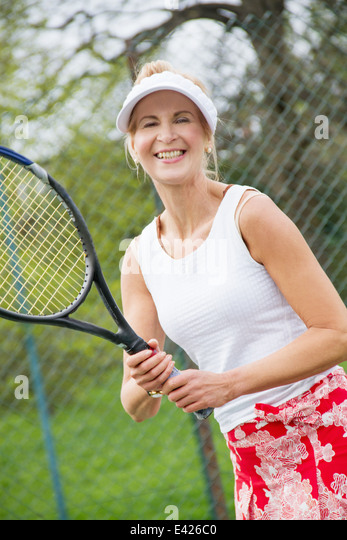 Portrait of mature woman playing tennis - Stock Image