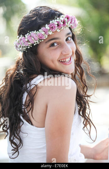 Young smiling teen with flowers in her hair - Stock Image
