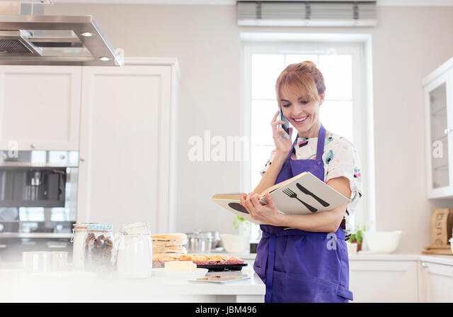 Female caterer with cookbook baking, talking on cell phone in kitchen - Stock-Bilder