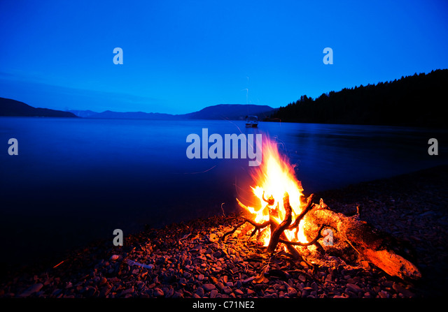 A beautiful camp fire burns at dusk against a deep blue lake with a wakeboard boat in the background in Idaho. - Stock Image