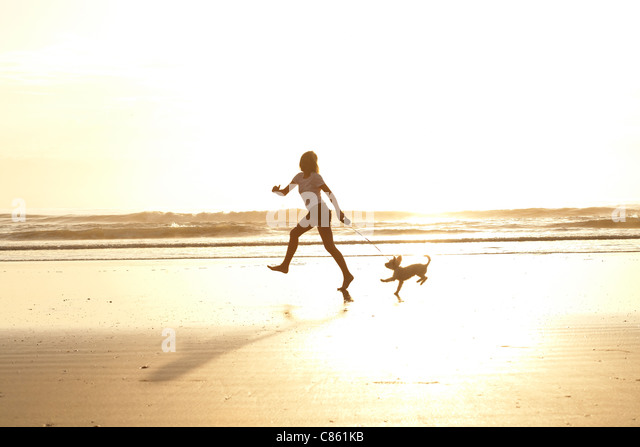 Girl running on the beach with her dog in the morning sunrise - Stock Image