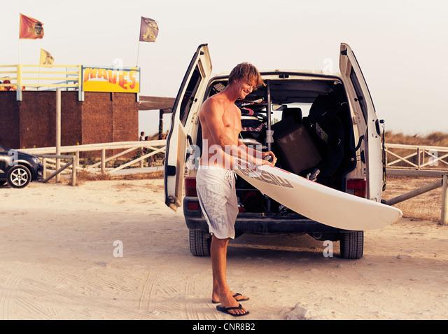 Man holding a windsurf board. - Stock Image