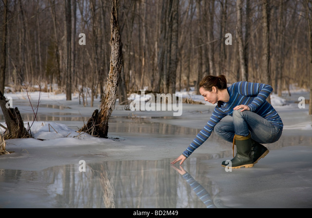 Woman Testing Melting Ice on Pond - Stock Image