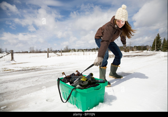 Woman dragging recycling in snow - Stock Image