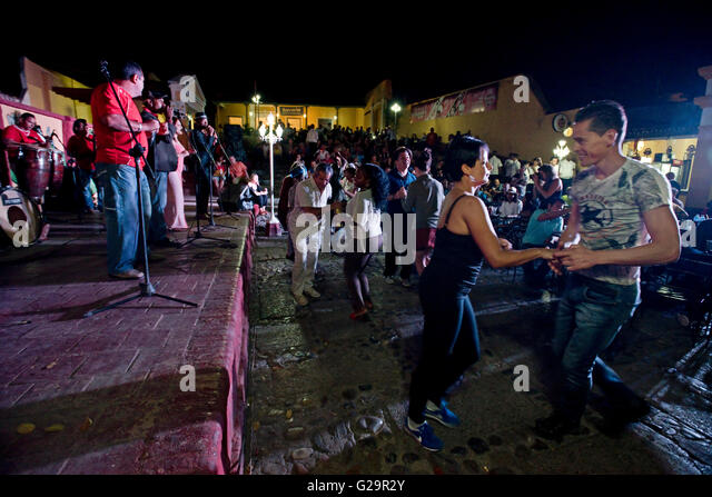 Cuban musicians in a group playing and singing salsa for locals and tourists at the Casa de la Músíca - Stock Image