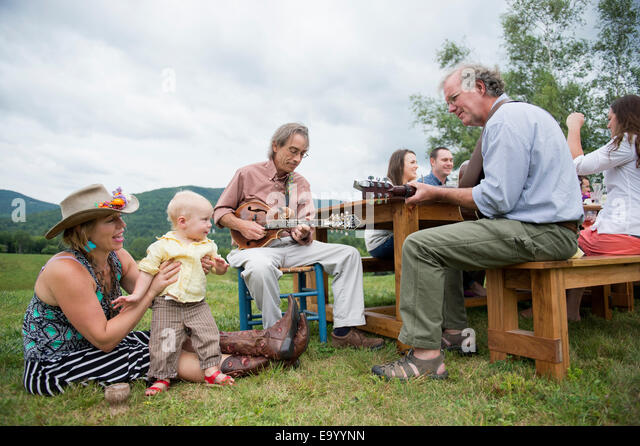 Two mature family members playing music at family meal, outdoors - Stock-Bilder