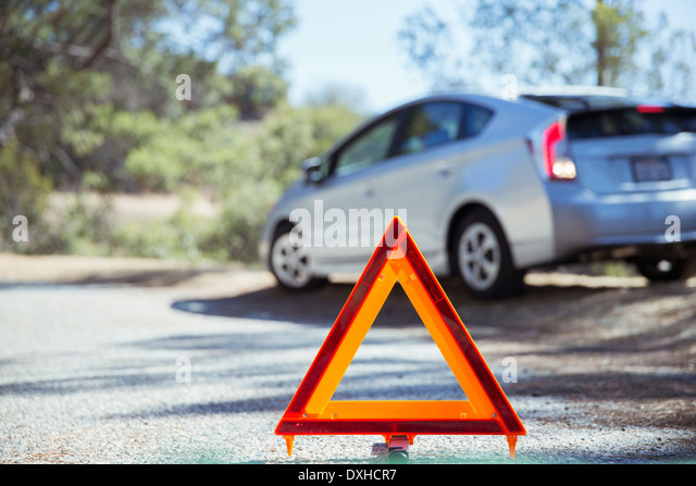 Car at roadside behind warning triangle - Stock Image