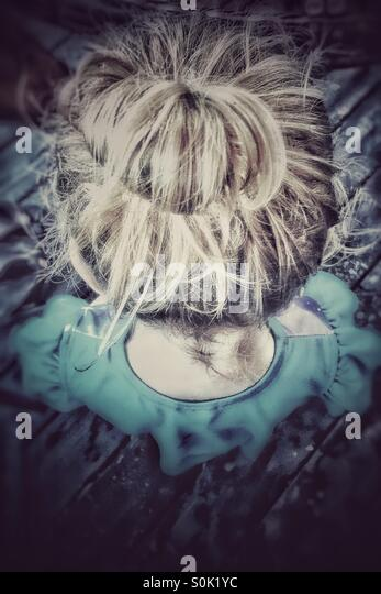Looking down at toddler with her hair in a bun - Stock Image