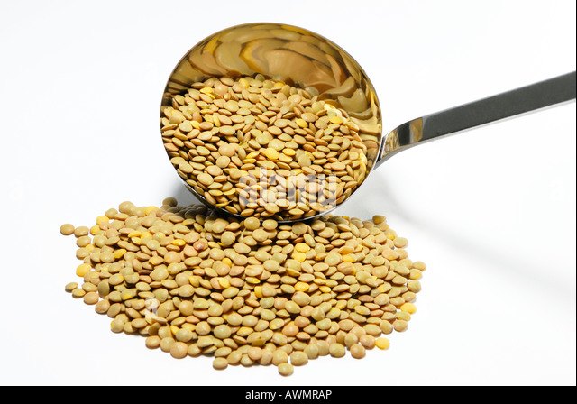 Dried brown lentils with a soup ladle - Stock Image