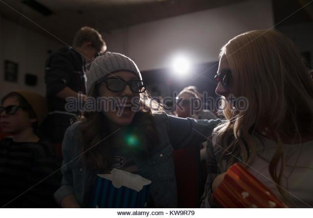 Laughing tween girl friends in 3d glasses watching movie,eating popcorn in dark movie theater - Stock Image