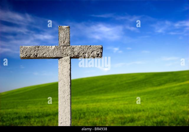 Religious stone cross on a beautiful green hill - Stock-Bilder
