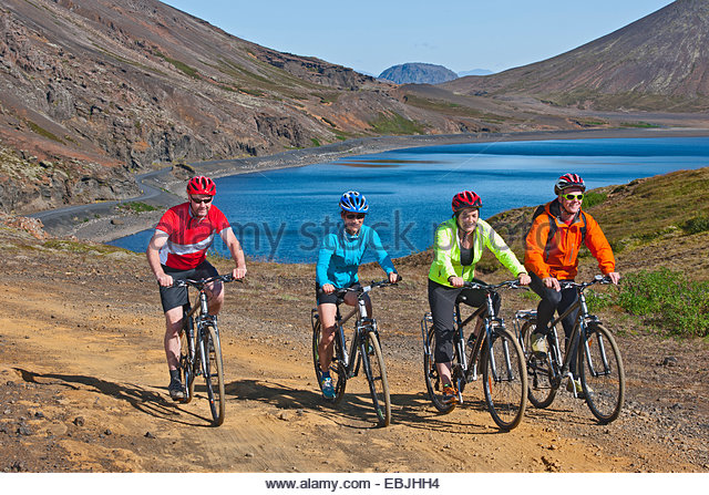 Cyclists cycling up track, Kleifarvatn in background, Reykjanes, South West Iceland - Stock Image