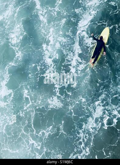 A surfer paddles out. Manhattan Beach, California USA. - Stock Image