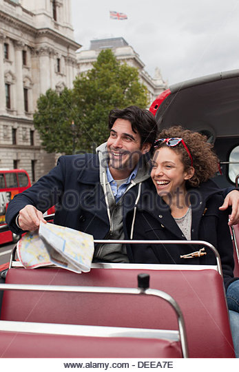 Couple riding double decker bus past Big Ben clocktower in London - Stock-Bilder