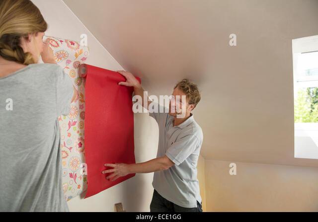 Man woman selecting wallpaper decorating - Stock Image