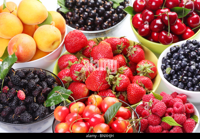 Different berries in bowls. - Stock Image