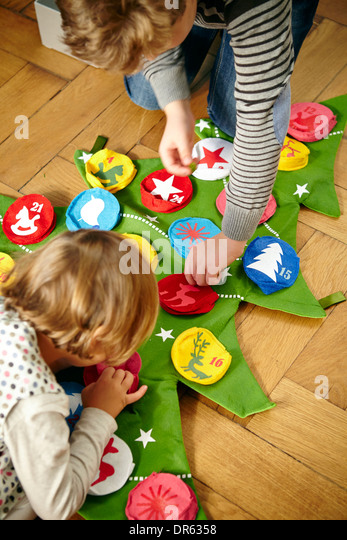 Children decorating Advent calendar, Munich, Bavaria, Germany - Stock Image