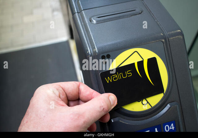 man using contactless merseytravel walrus card travel smartcard at train station entrance gate in liverpool - Stock-Bilder