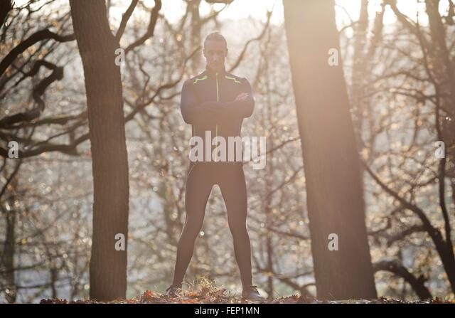 Full length front view of mid adult man standing in forest arms folded looking at camera smiling - Stock Image