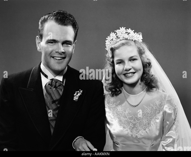 1940s PORTRAIT OF BRIDE AND GROOM LINKED ARM IN ARM LOOKING AT CAMERA - Stock Image
