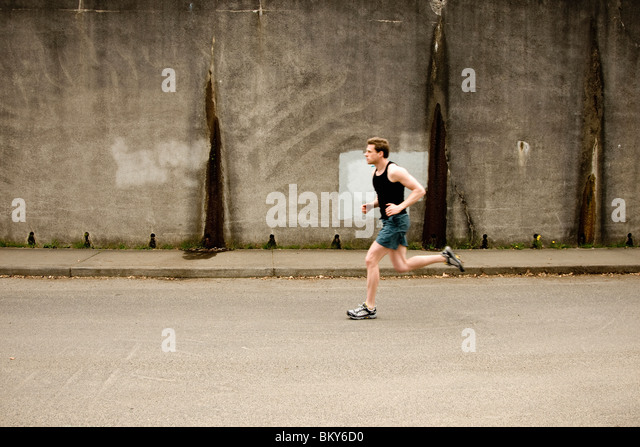 An athletic man jogging past a concrete wall in Portland, Oregon. - Stock Image