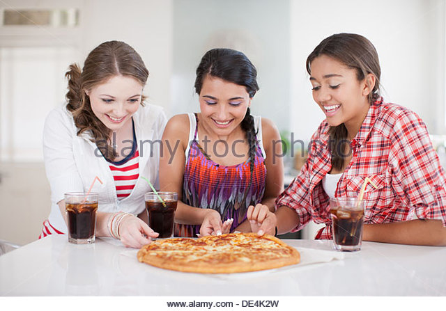 Teenage girls eating pizza - Stock Image