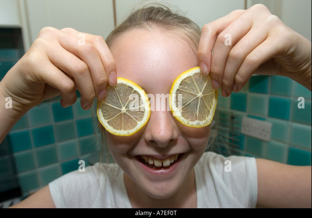 Young girl laughs as she places lemon slices in front of her face for eyes UK - Stock-Bilder