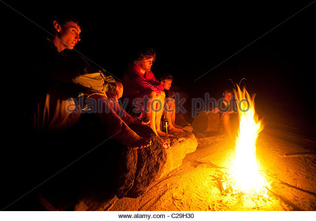 Kayakers sit around a campfire at a Congo River campsite. - Stock-Bilder