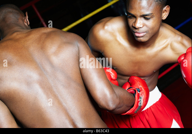 Two male boxers fighting in a boxing ring - Stock Image