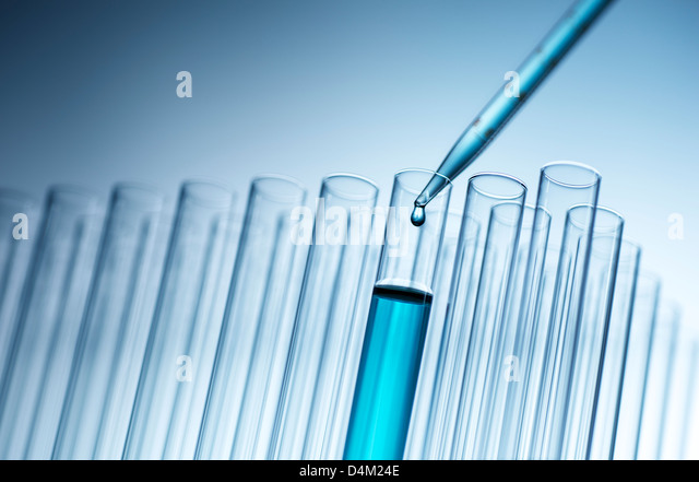 Medical pipette dropping liquid into test tube - Stock Image