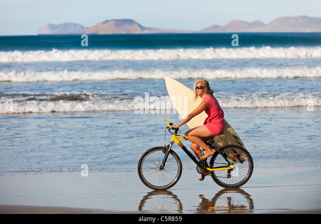 Surfer riding mountain bike along Oceans edge. - Stock-Bilder