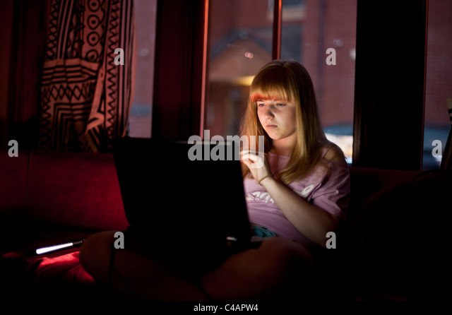 a teenage girl checking email facebook social networking on her laptop computer at home evening uk - Stock Image