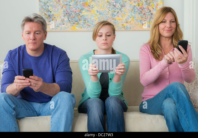 Family with teenage girl using communication devices - Stock-Bilder