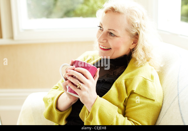 Woman with drink relaxing - Stock Image