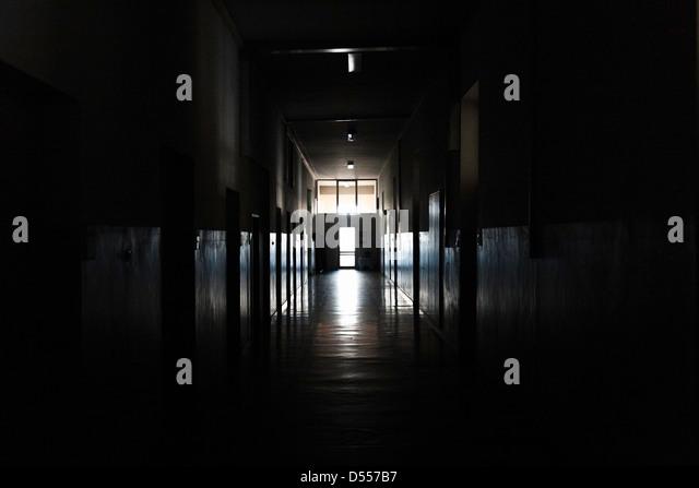 Light shining from door in dark hallway - Stock Image