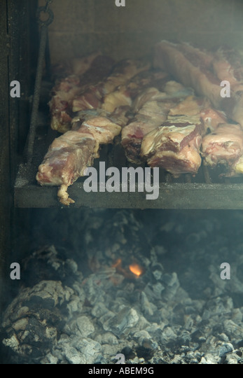 Meat grilling in barbecue - Stock Image