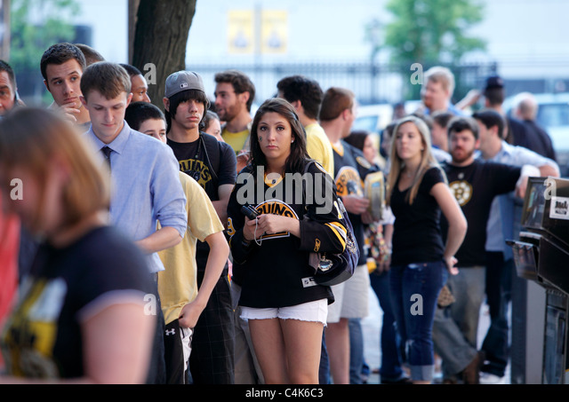 Boston Bruins hockey fans line up to enter a bar in Boston for game seven of the Stanley Cup being played in Vancouver - Stock Image