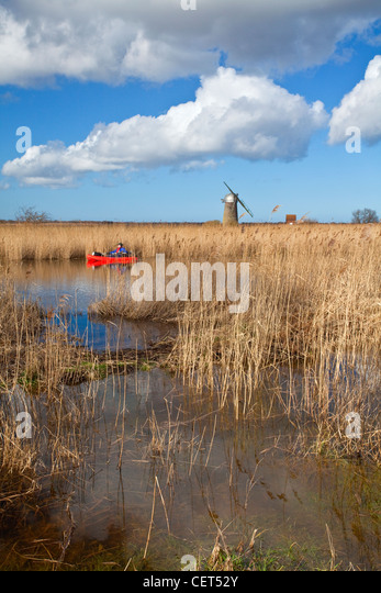 Canoeist on the River Thurne with the derelict Heigham Holmes Mill at Eelfleet Dyke in the distance on the Norfolk - Stock-Bilder
